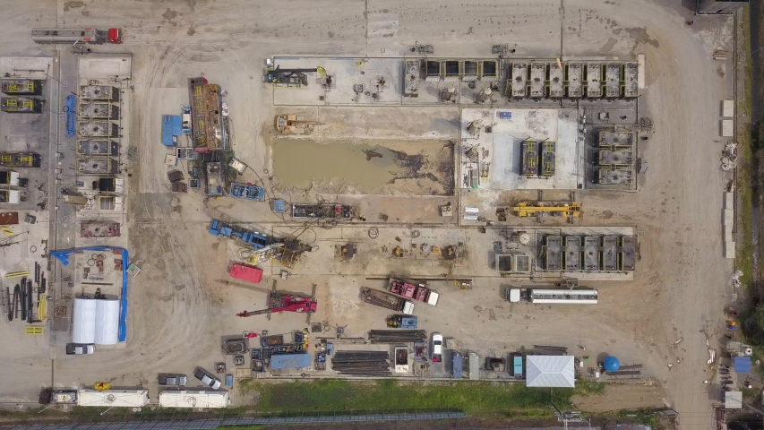 Oil and gas land drilling rig onshore in the middle of a rice field aerial view from a drone  | Shutterstock HD Video #1039561379