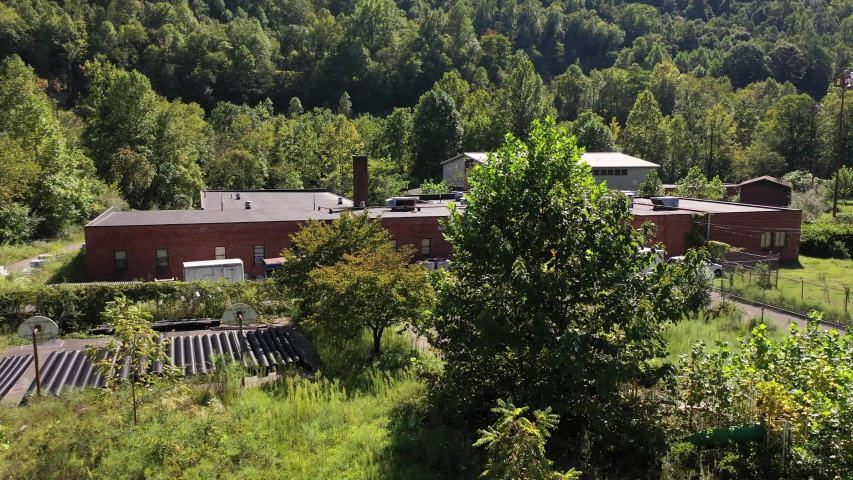 Aerial ascent in front of Marsh Fork Elementary School showing overgrown playgrounds in mountains of West Virginia.