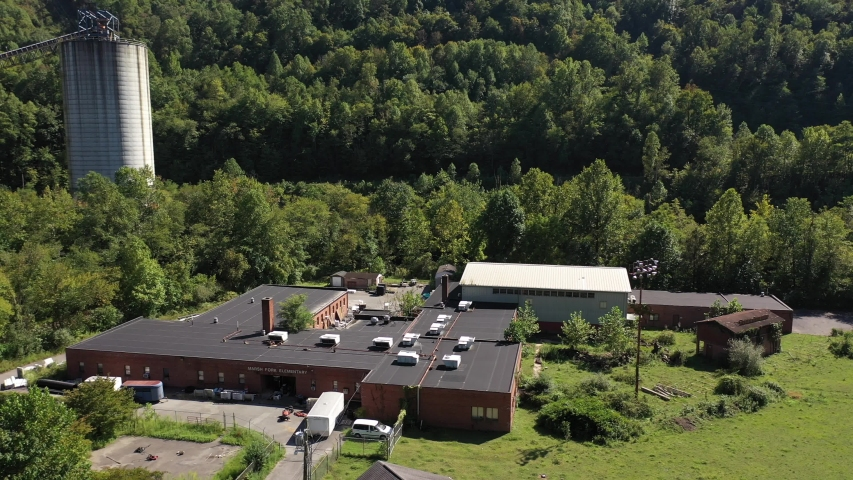 Aerial panning to left showing Marsh Fork Elementary School with coal slurry pipelines and towers looming over school in mountains of West Virginia.