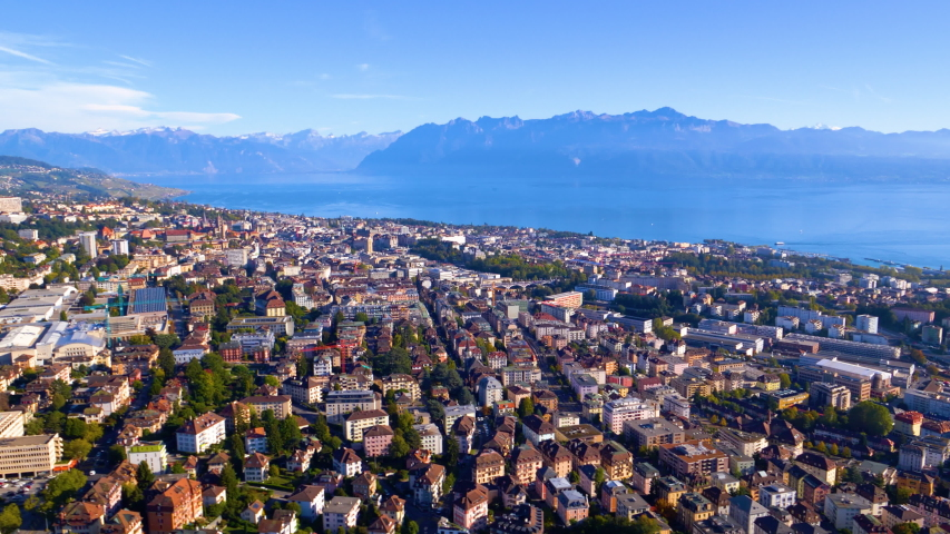 Aerial shot overflying Lausanne city descending towards train station, with Lake Leman and the Alps in background, Switzerland. Helicopter aerial shot.