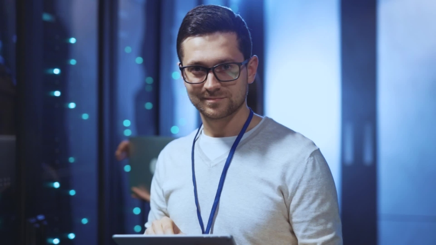 Positive IT administrator running diagnostics on tablet checking server rack system quality maintenance in modern data center. Portrait of cheerful smiling young engineer. | Shutterstock HD Video #1039586390