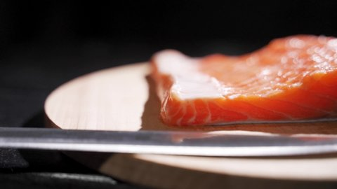 Chef takes out bones from the salmon fillet, cutting fish on slices for cooking sushi