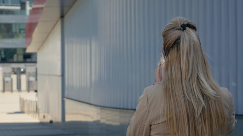 Unrecognizable woman talking on the phone against the background of modern buildings. The blonde with walks on the street, calls and conversation | Shutterstock HD Video #1039609598