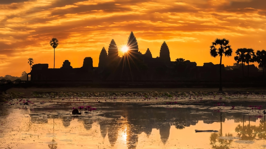 Angkor Wat, Siem Reap/Cambodia - February 2 2018: Sunrise at Angkor Wat Cambodia, with the reflecting pond in the foreground and the temple silhouetted with the sun rising by the main temple.