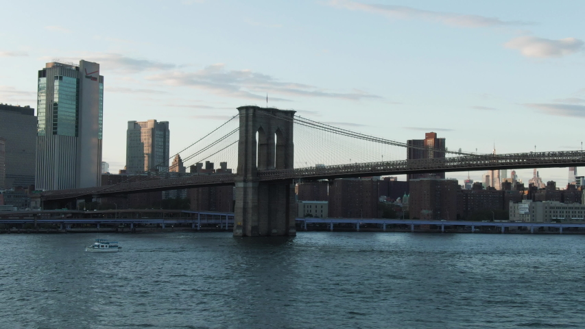 Wide angle aerial tracking shot of the Brooklyn Bridge with downtown Lower Manhattan, New York City in the background at dusk on a clear summer evening. | Shutterstock HD Video #1039619810