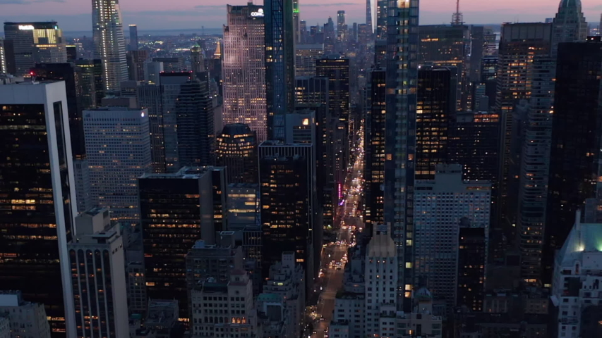 AERIAL: Manhattan Skyline at night with flashing city lights in New York City over Central Park in beautiful 4K