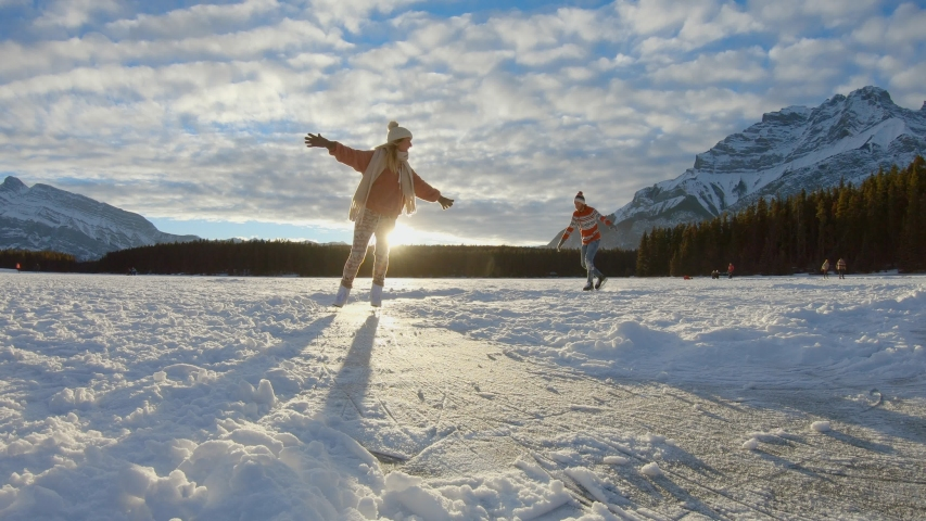 Young couple ice skating in winter outdoors on a frozen lake in Canada