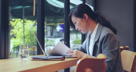 Side view pretty Asian businesswoman working in the office by the window using laptop searching internet Chinese business working woman reading document and writing notes 4k clip adult keep learning