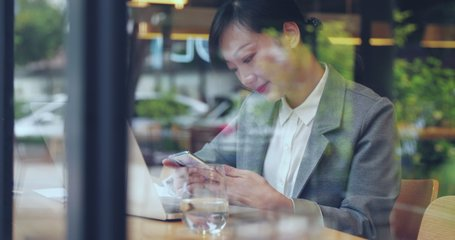 Through the office window view of pretty business asian woman using mobile phone in cafe Chinese businesswoman browsing social media happy smile urban lifestyle 4k clip