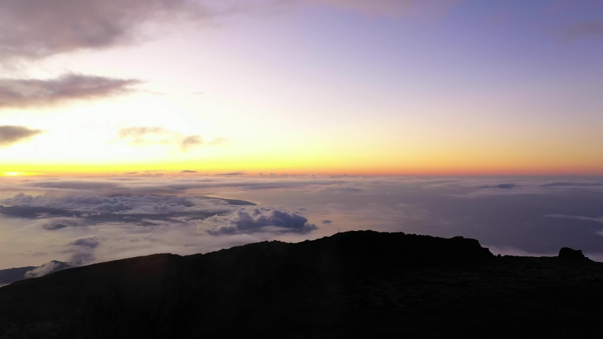 Aerial view from top of mountain Pico, revealing the Azores island with a purple twilight due to volcanic gases.