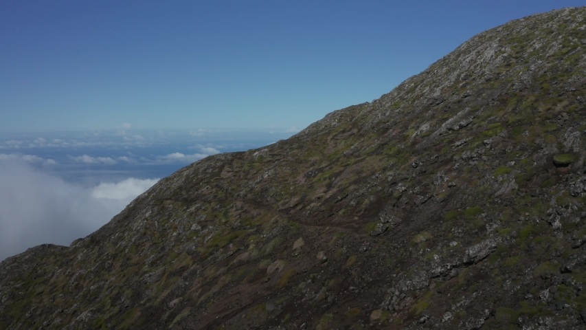 Aerial Drone flying around Pico Mountain near clouds with rocky ground detail.