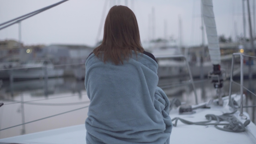 Beautiful red-haired woman sitting in a plaid on a yacht in the French port. Yachts in the background | Shutterstock HD Video #1039649900
