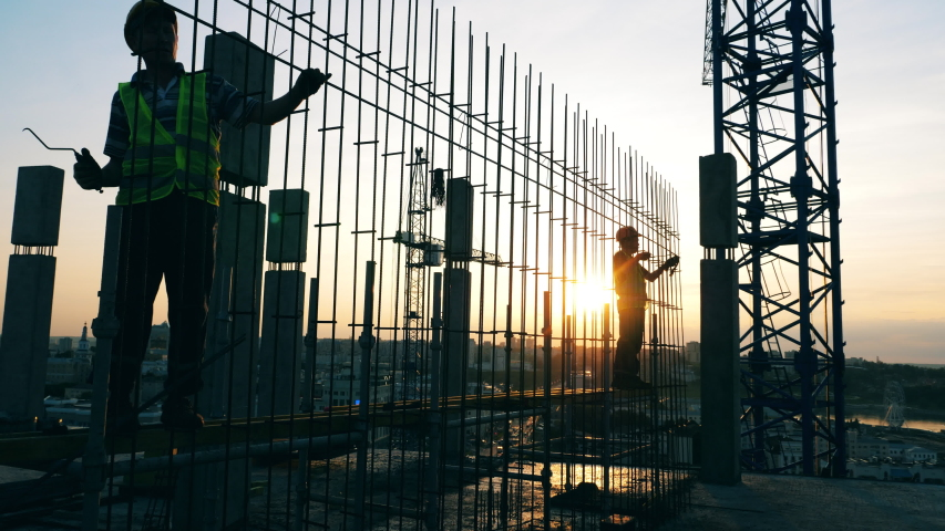 Sunset construction site with engineers fabricating a framework | Shutterstock HD Video #1039651073