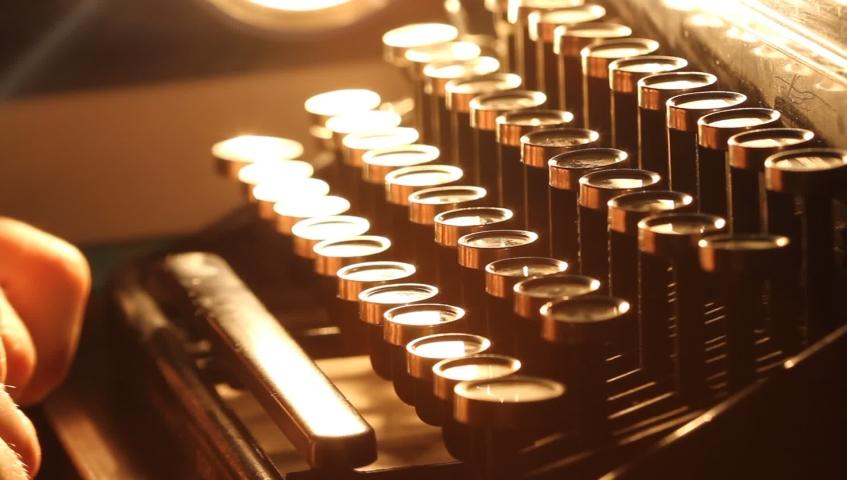 Close up shot of man typing on old vintage retro typewriter; backlit; news, media or communication concept | Shutterstock HD Video #1039664402