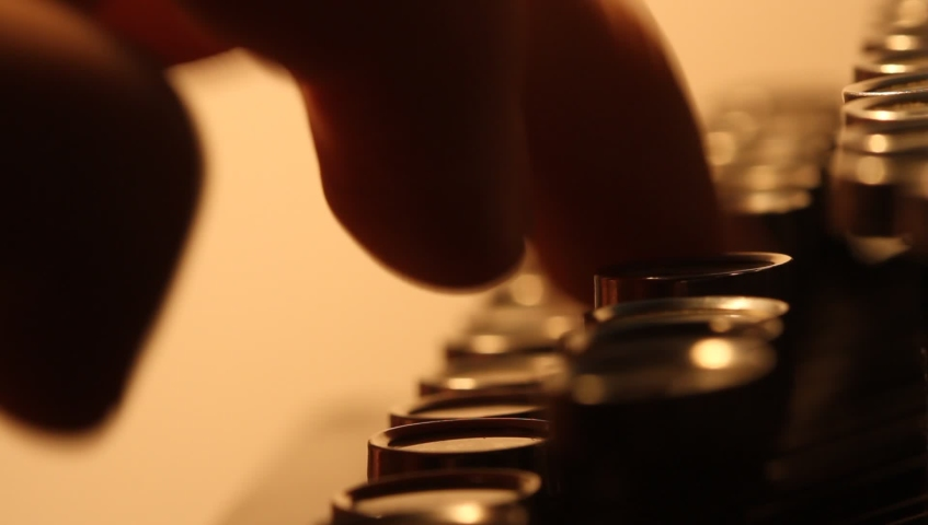 Close up shot of man typing on old vintage retro typewriter; backlit; news, media or communication concept | Shutterstock HD Video #1039664405