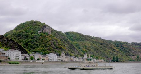 A boat passes in front of a small German village in the middle Rhine valley in Bavaria, Germany. A castle can be seen on the mountain in the distance.