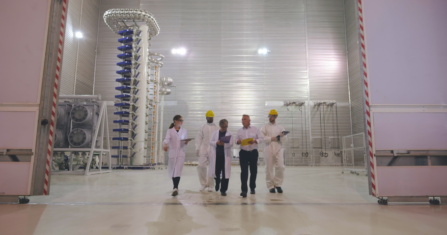 Multiethnic team of researchers working in modern innovative laboratory. Scientists and workers walk through huge secret lab and discuss equipment and results of experiment International cooperation | Shutterstock HD Video #1039685432