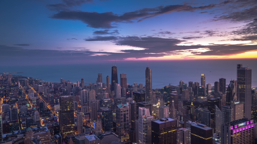 Chicago panoramic skyline aerial view timelapse from early morning with city lights on to a beautiful sunrise with colorful pink, blue, orange and purple clouds above and Lake Michigan beyond.