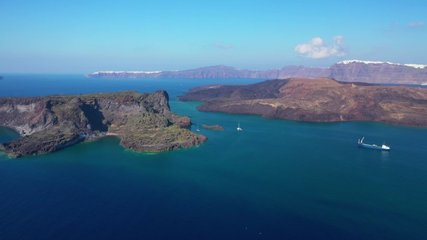 Aerial drone video of volcanic islet of Kameni in iconic Santorini island, Cyclades, Greece