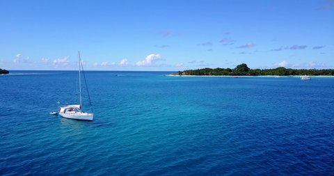 Sail boat off the coast of small tropical island in the caribbean