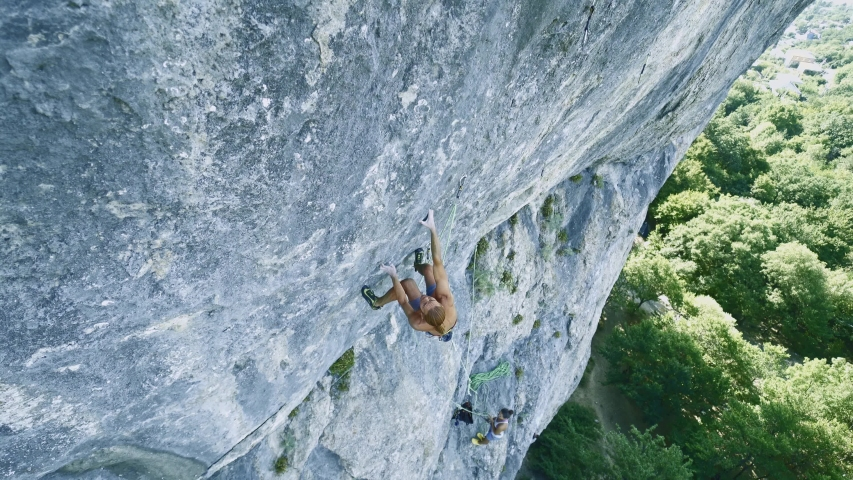 Strong muscular man rock climber dynamically climbing on a limestone cliff, making several hard wide moves, gripping holds, and falling. outdoors rock climbing and active lifestyle concept, wide angle | Shutterstock HD Video #1039719947