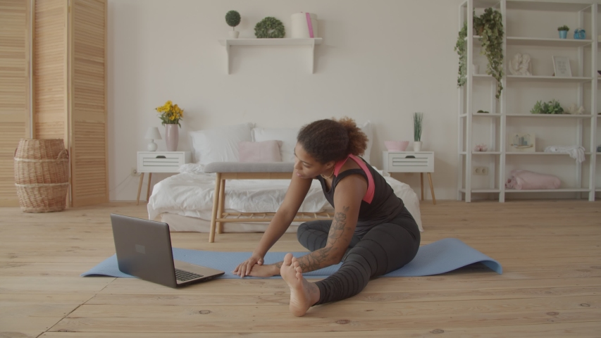 Determined sporty african american woman working out, doing stretching exercise on yoga mat while watching fitness video online on laptop at home. Female practicing yoga exercise online with laptop pc