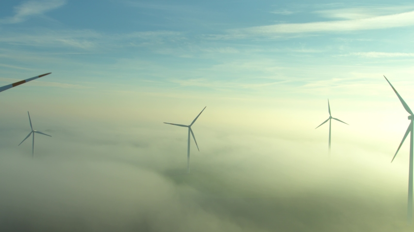 Camera flying along rotating wind wheels in backlit with ground fog | Shutterstock HD Video #1039731746