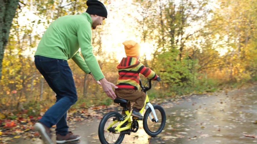 Father teaches his little child to ride bicycle in autumn park. Happy family moments. Time together dad and son. Candid lifestyle footage.  | Shutterstock HD Video #1039739789