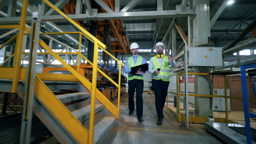 Engineers walk in a factory facility, checking brick factory machines. #1039740050