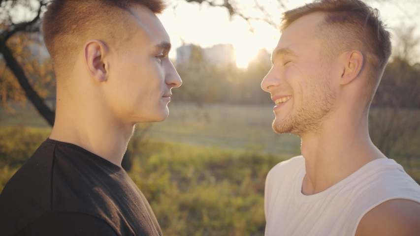 Close-up faces of two Caucasian strong men looking at each other in sunlight and laughing. Adult sport boys standing outdoors in the autumn park. Healthy lifestyle, sport concept. | Shutterstock HD Video #1039750226