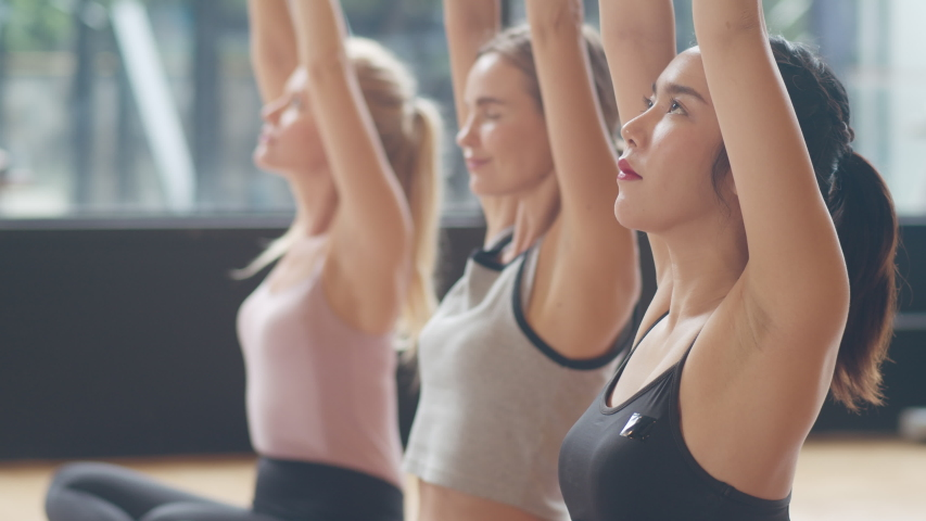 Young diversity sporty people practicing yoga lesson with instructor. Multi racial group of women exercising healthy lifestyle in fitness studio. Sport activity, gymnastics or ballet dancing class. | Shutterstock HD Video #1039751681