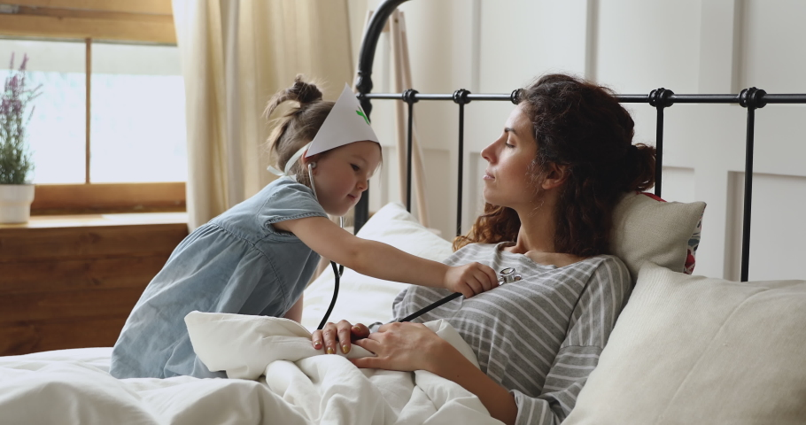 Cute funny little kid girl playing as doctor holding stethoscope listening happy mom lying in bed, playful child daughter wear medical hat pretending nurse having fun with mother in bedroom at home