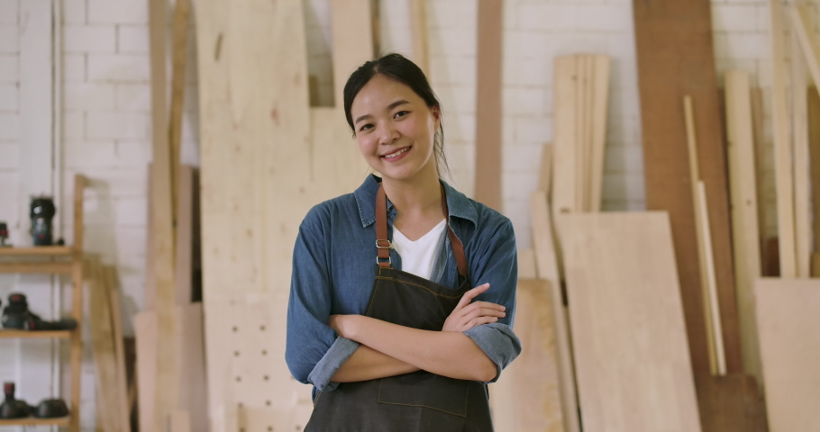 Close-up portrait of young attractive carpenter standing with crossed arms smiling positively into camera. Slow motion | Shutterstock HD Video #1039777544