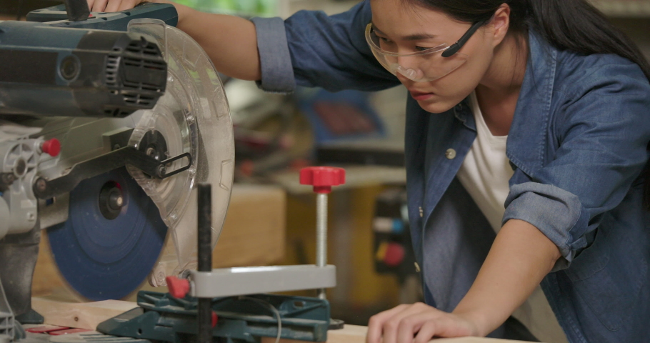 Young asian female carpenter cutting wooden plank with a circular electric saw in carpentry workshop. 4k Slow motion. | Shutterstock HD Video #1039777565