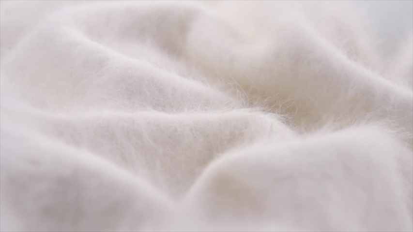Soft Wool background. Alpaca wool mohair clothes texture closeup. Natural Cashmere Soft and fluffy merino wool macro shot. Woolen fabric rotation backdrop. Slow motion UHD 4K