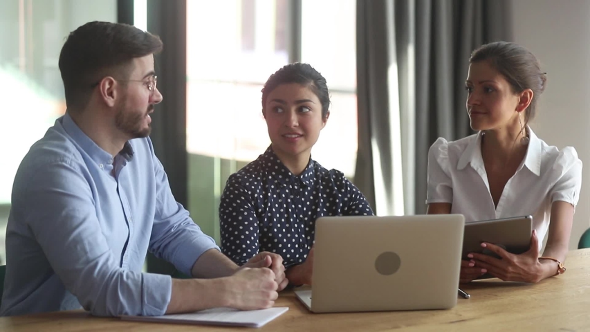 Indian and european female colleagues listening team leader or mentor during meeting in office room, multi-ethnic associates working together discussing project task sitting at desk, teamwork concept Royalty-Free Stock Footage #1039779362