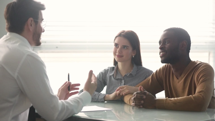 Happy multiracial couple finish formal business meeting in bank sign mortgage contract make financial deal affirm agreement feels satisfied buy new first property accomplish negotiations shaking hands Royalty-Free Stock Footage #1039779374