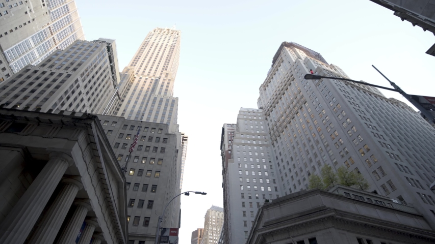 New York City , New York / United States - 10 02 2019: Moving through crowded FINANCIAL DISTRICT of NEW YORK CITY to a low angle shot of the WALL STREET skyscrapers