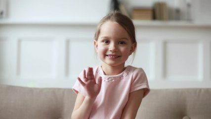 Little 6 years old cutie girl sitting on couch wave hand greeting friend or relative person feels shy, answering questions using online telecommunications application video call virtual talk concept