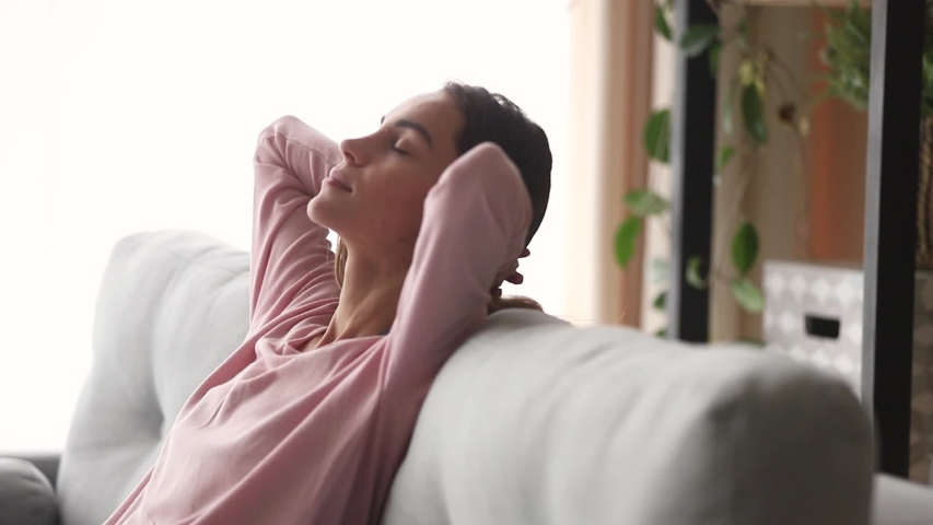 Moving camera slider showing side view relaxed millennial woman falling asleep closed eyes putting hands behind head leaned on couch enjoy day nap in living room, resting at home renew energy concept #1039785860