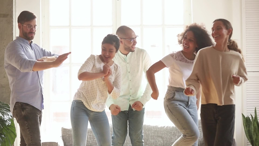 Active diverse cheerful friends listen favourite track moving dancing in living room enjoy life and free time together fool around laughing, multi-ethnic friendship like-minded people have fun concept | Shutterstock HD Video #1039785881