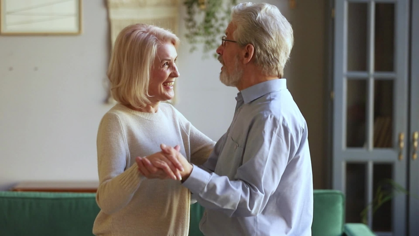 Elderly spouses having pleasant conversation share memories during waltz dancing, hoary husband in glasses hugs the waist holds hands of beloved wife chatting enjoy life active weekend at home concept Royalty-Free Stock Footage #1039788443