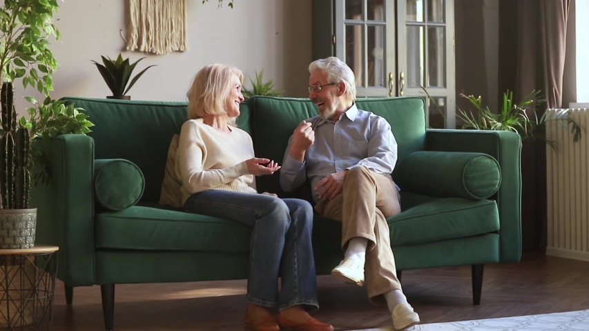 European attractive elderly couple old family wife and husband sitting on couch in cozy light living room having pleasant warm conversation talking share memories spend time together at home concept