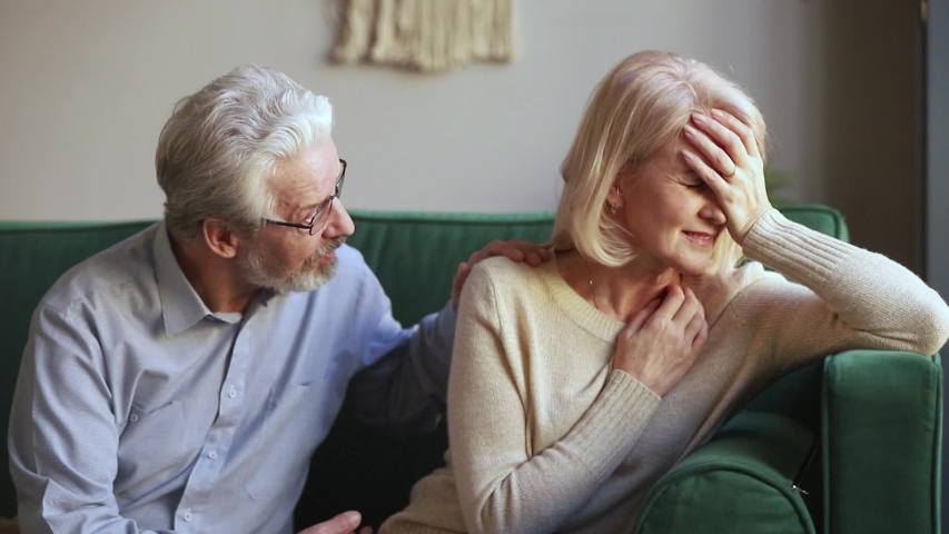 Elderly spouses sitting on couch aged wife crying feels desperate worried anxious husband comforting beloved woman showing empathy, sad life event, senile disease diagnosis, health problems concept