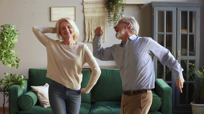 Elderly spouses standing in living room listening energetic music dancing together, senior hoary rock-n-roll dancers enjoy life feels happy and healthy spending active free time on weekend at home Royalty-Free Stock Footage #1039788467