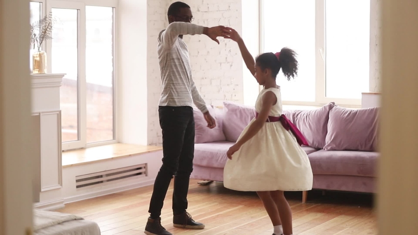 Two positive african relative people different age guy and girl enjoy free time together standing in living room, loving father gentle touch holds hand of pretty preschool daughter swirls her dancing #1039791071