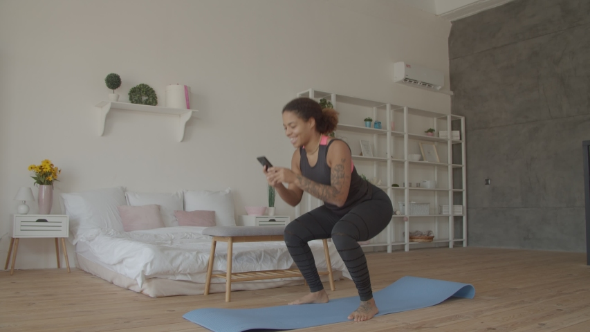 Multitasking sporty fitness african american woman doing squats and browsing online on smart phone in loft apartment. Busy with cellphone fit attractive black female working out and squatting at home. | Shutterstock HD Video #1039791191