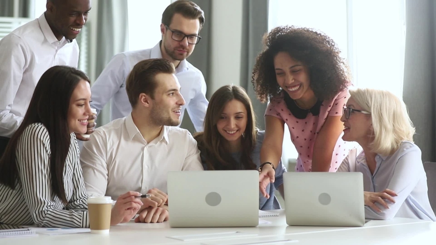 Multi racial employees gathered together in boardroom or co-working space listening mixed race millennial female team leader showing on laptop new software explain program or shares sales growth sales