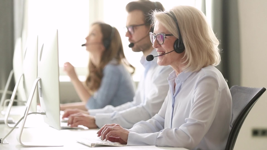 Aged woman call center employee sitting at workplace having busy workday, sales agent wearing headset use computer typing search information provide help to client distantly helpline office concept