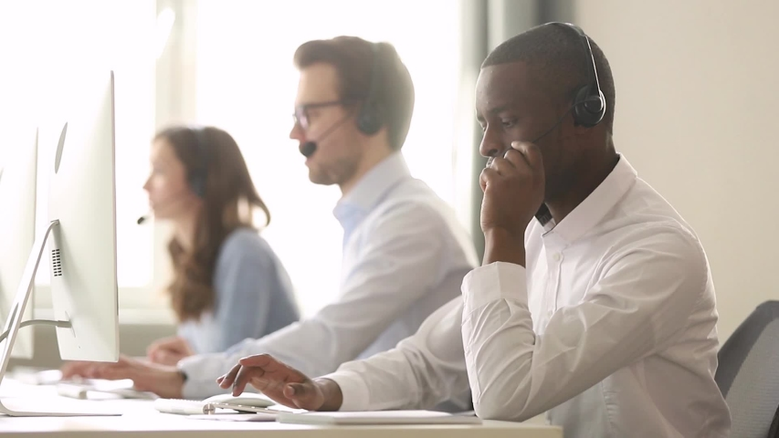 Call center diverse employees working in shared desk focus on african worker wearing headset typing look at pc screen talk help to company client distantly, provide information helpline office concept